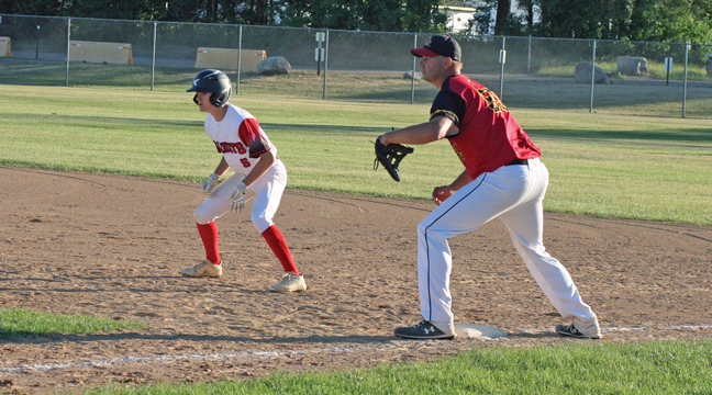 Bandit Jacob Bergsten leads off first base in the seventh inning as Buzzard 1B Matt Koester readies for a possible pickoff play.  (Patriot photo by Mark Kolbinger).