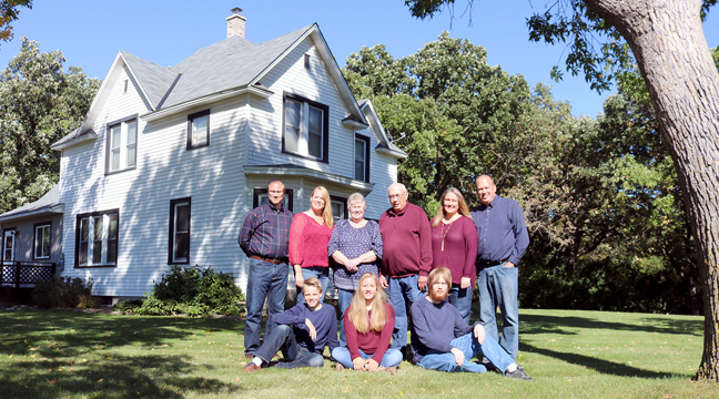 JIM AND SHARON LEE (TOP, CENTER) with their family in front of the farmhouse built by Jim's grandparents. (Submitted photo.)