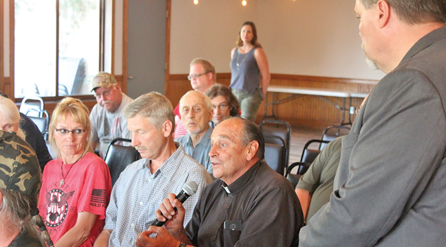 JIM NEWBERGER (R) trekked through the crowd Tuesday, allowing guests to ask questions or make comments during the Townhall meeting at Pebble Creek. (Patriot Photo by Bill Morgan)