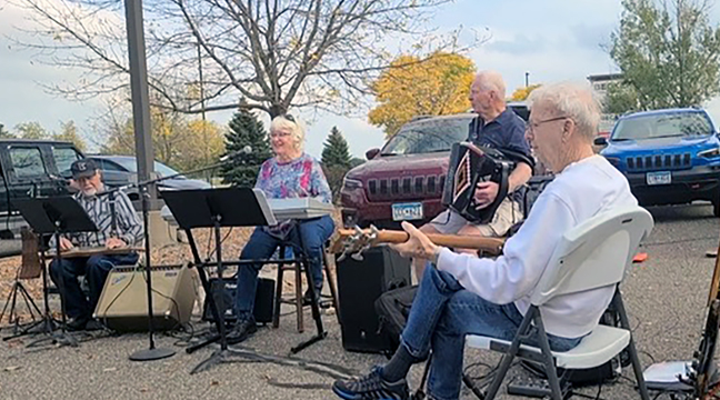 A CROWD OF PEOPLE set up chairs and enjoyed listening to the old time band consisting of members Richard Eckman (steel guitar), Kittie Fenlason (keyboard), Travis Kent (accordion) and Don Swendsrud (electric guitar). (Photo by Mary Nehring.)