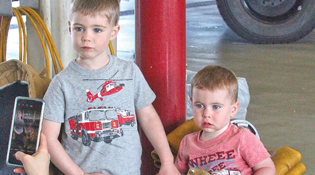 FOUR-YEAR-OLD BRYSON ODLE (L) AND HIS TWO-YEAR-OLD BROTHER, DAXTON  (R) of Becker took turns trying on firefighter gear and posing for pictures for their mom, Tracy (far left) during Saturday's Becker Fire Open House. (Patriot Photo by Bill Morgan.)