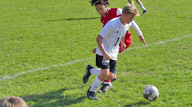 Evan Norberg worked his way past the competition in a recent game for the Becker Bulldog boys soccer team. (Submitted photo.)