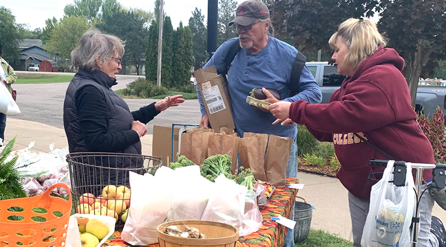 MARY BERGERON helps customers with their fresh produce purchases during Rejoice's Fall Festival last Saturday.(Photo by Penny Leuthard.)