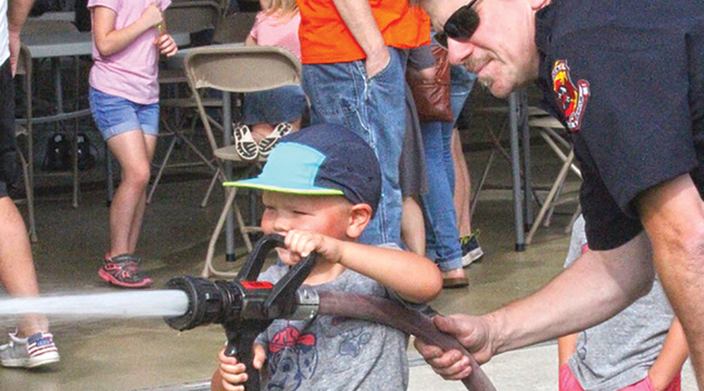 FOUR-YEAR-OLD EASTON SYTSMA OF BECKER stayed focused as he guided the fire hose on a wooden structure a few feet away. Easton was at the Becker FD Open House with his mom, Molly (not shown). (Patriot photo by Bill Morgan.)