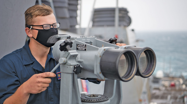 Boatswain's Mate Seaman Evan Sand, from Clearwater, MN, uses the ship's binoculars to search for contacts on the bridge-wing of the guided-missile destroyer USS Barry (DDG 62) as the ship conducts routine underway operations in the Taiwan Strait. Barry is assigned to Destroyer Squadron (DESRON) 15, the Navy's largest forward-deployed DESRON and the U.S. 7th Fleet's principal surface force, forward-deployed to the U.S. 7th Fleet area of operations in support of a free and open Indo-Pacific. (U.S. Navy photo by Lieutenant Junior Grade Samuel Hardgrove).