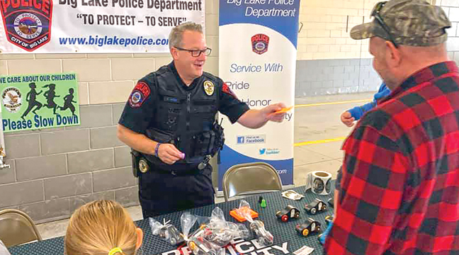BIG LAKE PD INVESTIGATOR RICH BERG manned the BLPD booth and handed out stickers and freebies at Sunday's BLFD Open House. (Photo from BLFD Facebook page).