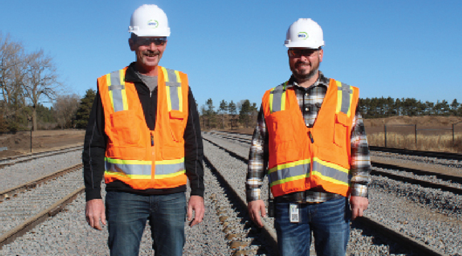 SCOTT HELBERG AND JAKE HANSEN of Northern Metals Recycling stood on the new tracks behind the Northern Metals Recycling facility in Becker. (Photo by Katherine Cantin.)