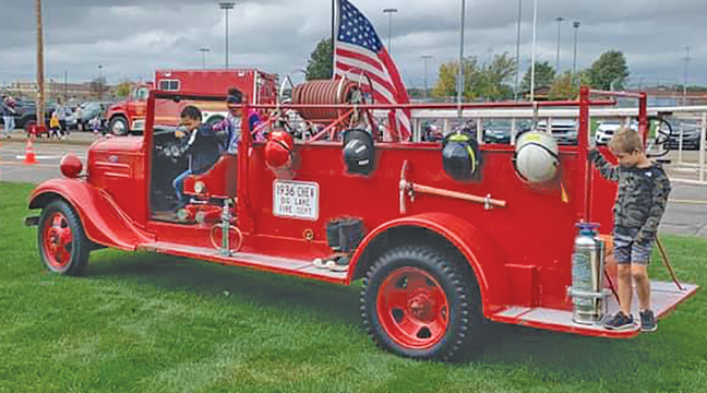 TONS OF KIDS climbed aboard a vintage, 1936 fire truck and checked out the gear from the days of yore during the Big Lake FD Open House Sunday. (Photo from BLFD Facebook page).